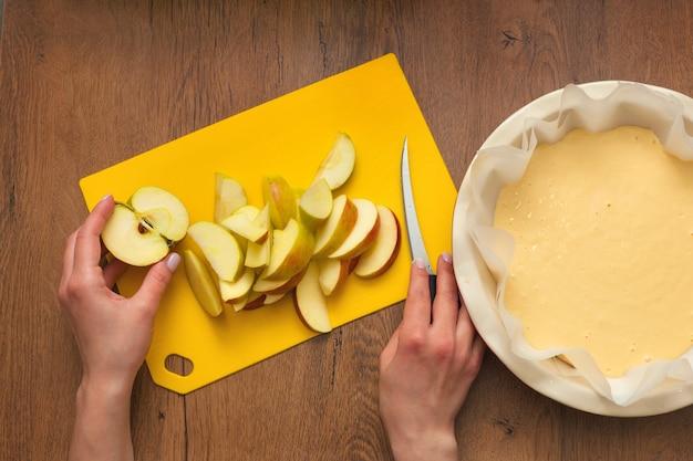 집의 여주인이 부엌에서 사과 샬롯을 준비하고 있습니다. 사과 파이에 재료를 넣습니다