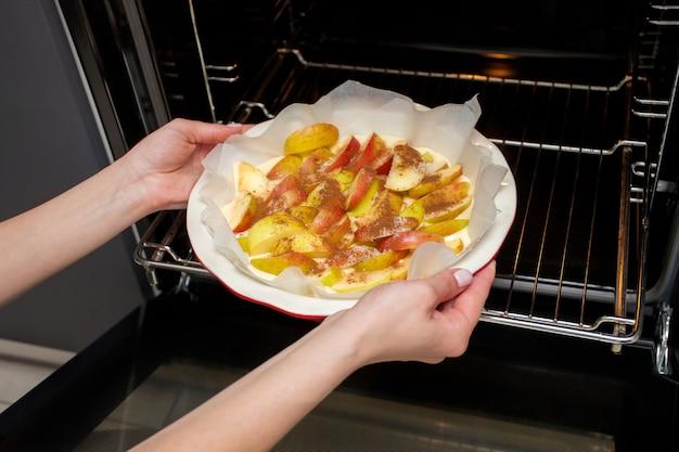 여주인은 집에서 부엌에서 사과 샬롯을 준비하고 오븐에 사과 파이를 넣습니다.