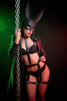 Горячая брюнетка позирует на темном фоне в поясе и маске кролика с цепями