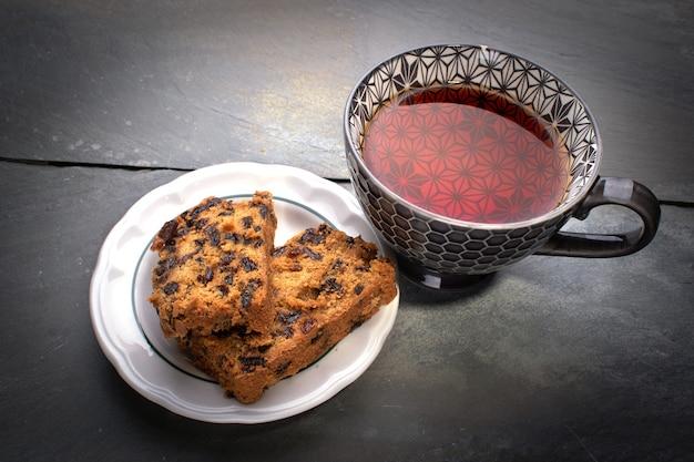 Чашка горячего чая и два ломтика фруктового торта на столе из старой шиферной плитки