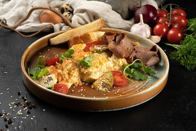 아침 식사를위한 뜨거운 메인 코스는 스크램블 드에 그, 야채, 허브로 만듭니다.