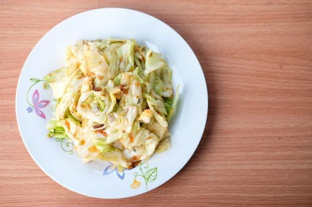 Капуста зажаренная горячим stir с соусом рыб служит на белом блюде установленном на коричневую таблицу - домодельную концепцию еды.