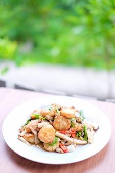 温かい炒め豆腐と豚肉とキノコの黒豆ソースがけ茶色のテーブル-自家製食品のコンセプトに設定された白い皿に提供しています。