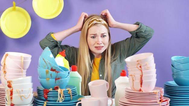 Домохозяйка в панике держит голову руками и смотрит на стол с горой грязных немытых тарелок и посуды
