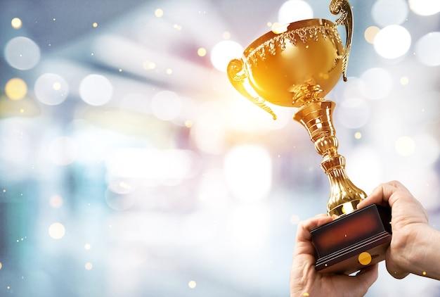 人間の手はチャンピオンの黄金のトロフィーを持っています。成功のコンセプト。