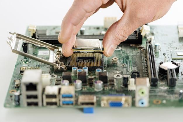 인간의 손이 마더보드에 프로세서를 설치하고 있습니다.