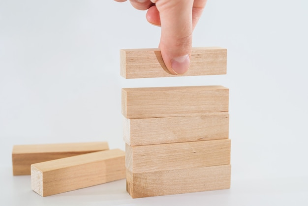 인간의 손이 나무 블록을 눕 힙니다. 사업 개발 개념