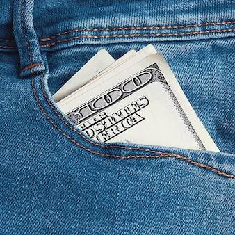 百ドル札は彼のブルージーンズの後ろのポケットに半分に折りたたまれています。画像全体のクローズアップ。フルフレームのカラー画像。