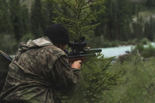 Охотник целится из ружья. мужчина в камуфляже готовится к стрельбе. охота в лесу со снайперской винтовкой