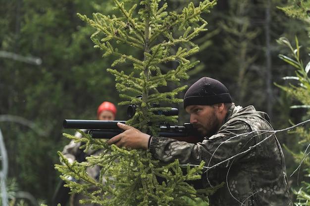 사냥꾼은 손에 카빈총을 들고 매복에 앉아 있습니다. 그 남자는 저격 소총을 쏠 준비를 하고 있다