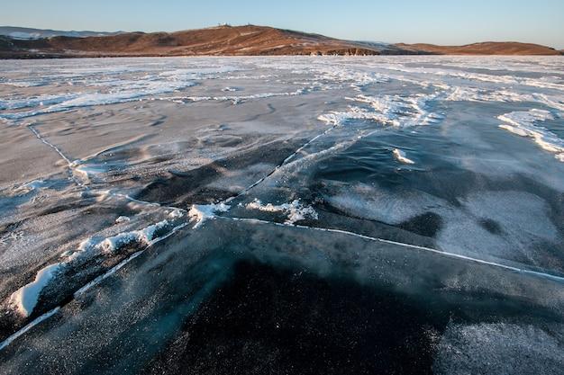 Ледяная гладь байкала зимой с большими трещинами, снегом и холмами на заднем плане. видна толщина льда. солнечная погода, ясное небо.