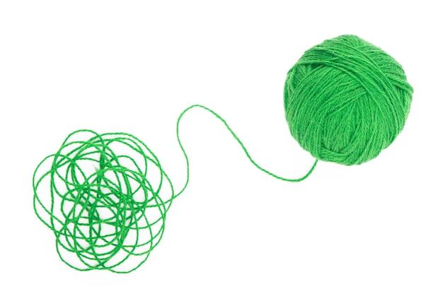 アイデアは絡み合った糸です。白い背景の上の糸の緑のボール