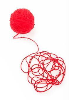アイデアは絡み合った糸です。白い背景の上の糸の赤いボール