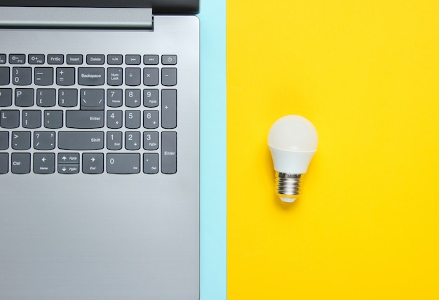 ビジネスコンセプトのアイデア。青黄色のテーブルにノートパソコンと電球。上面図