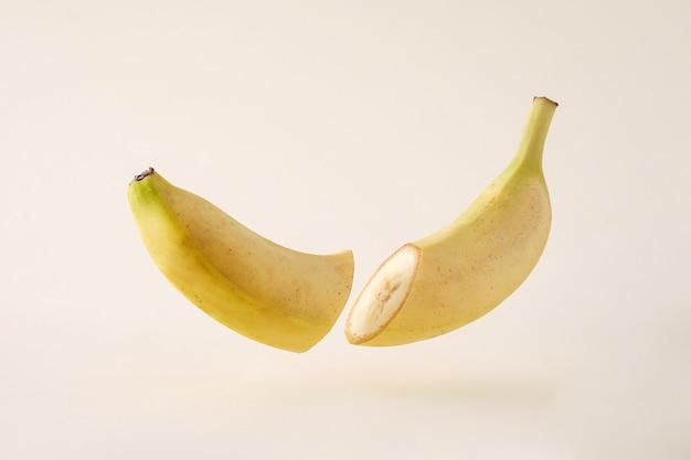 둘로 쪼개지고 공중에 떠 있는 바나나의 아이디어는 크림 같은 배경 위에 자유롭게 공중에 떠 있습니다.