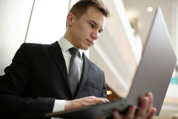 モールで黒いスーツを着て、ラップトップで働く真面目な学生の画像
