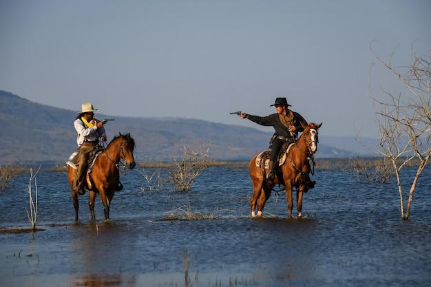 카우보이 액션의 이미지는 말을 타고 손에 총을 들고 있습니다.