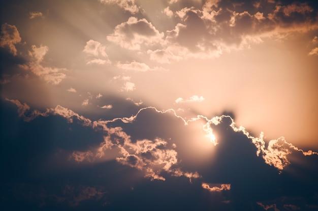 日没前の夕方の黄金の空の画像。雲が太陽を覆い隠している