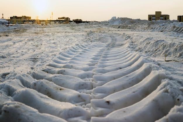 Отпечаток протектора колес трактора на снегу.