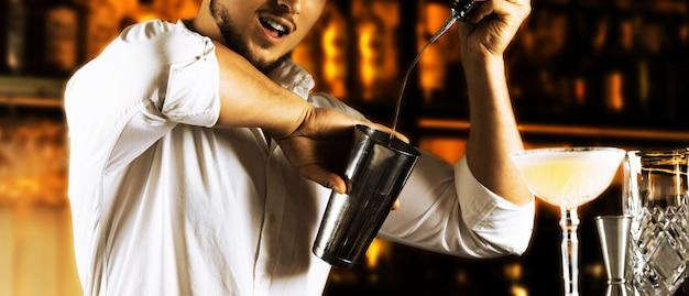 방화 바텐더는 병의 알코올을 셰이커에 아름답게 붓고 손님을 위해 쇼의 현재 불꽃을 준비합니다. 혼합 매체