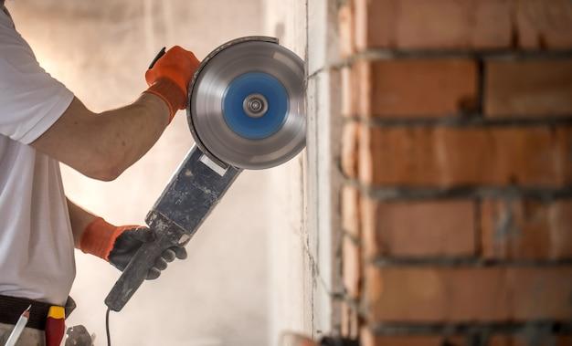 산업용 빌더는 전문 앵글 그라인더와 함께 작업하여 벽돌을 자르고 내부 벽을 만듭니다. 전공.