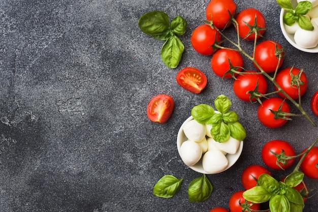 カプレーゼサラダの材料。バジル、モッツァレラチーズのボール、コピースペースと暗いコンクリートの背景にトマト。