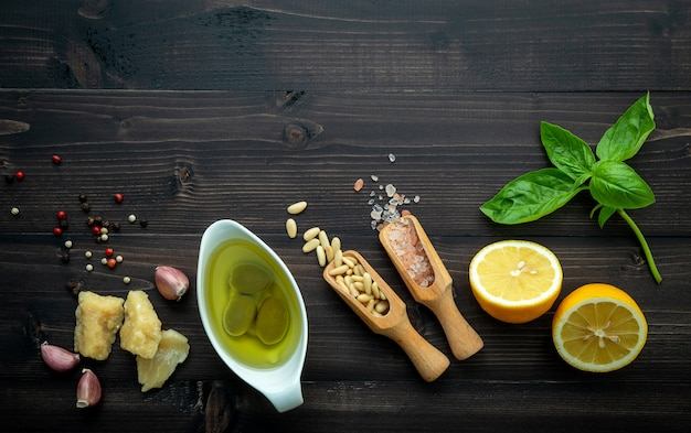 Ингридиенты для зеленого соуса песто на темной деревянной предпосылке.
