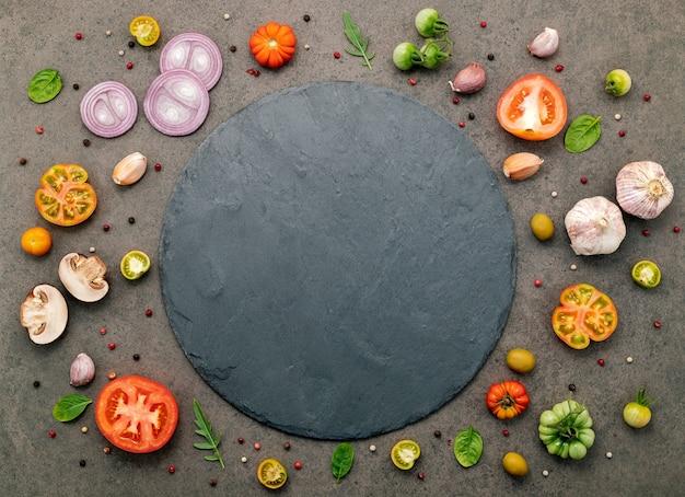 홈메이드 피자의 재료는 어두운 돌 배경에 설정되어 있습니다.