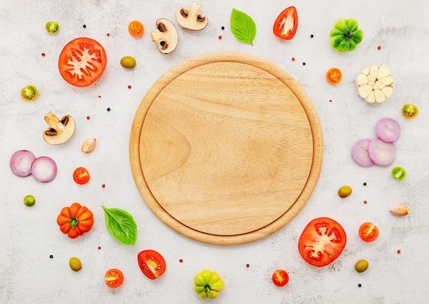 홈메이드 피자의 재료는 흰색 콘크리트 배경에 설정되어 있습니다.