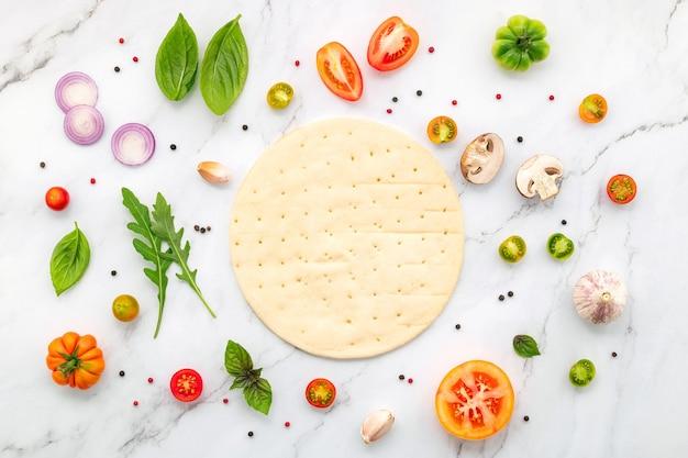 Ингредиенты для домашней пиццы на белом мраморном фоне.