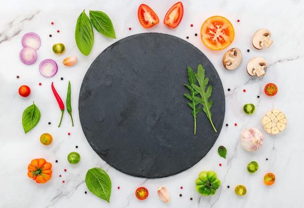 수제 피자 재료는 흰색 대리석 배경에 설정되어 있습니다.