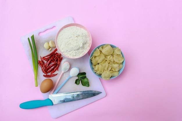 파스텔 핑크 배경으로 맛있고 맵지 않은 인도네시아 스낵을 만들기 위한 재료