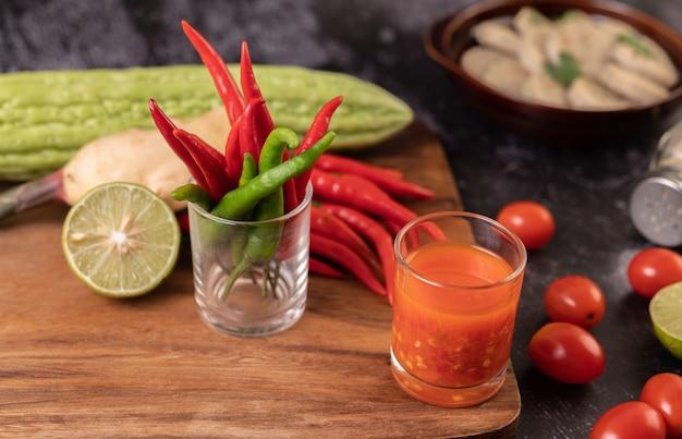 Ингредиенты, используемые для салата, включают помидоры, перец, лайм и горькую тыкву.