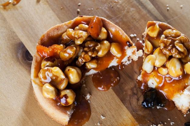 В тарталетке используются фундук, арахис, курага, чернослив, грецкие орехи, тарталетка круглой формы с орехами и сухофруктами, залитая карамелью.