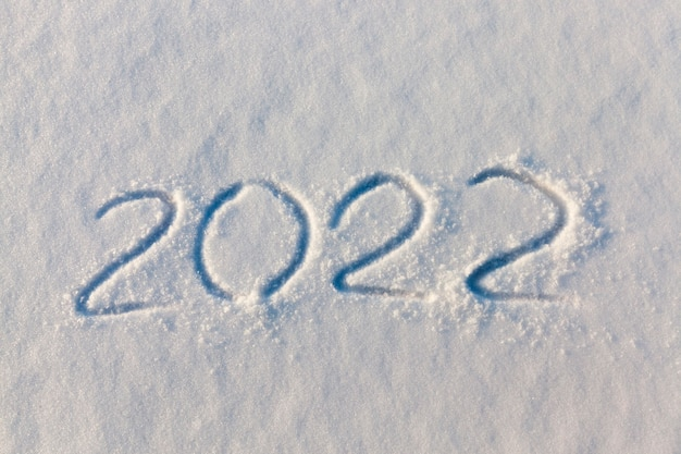 冬の雪の上の2022年の新年についての碑文、2021年の終わりの冬の季節と2022年の始まりの新年についての碑文