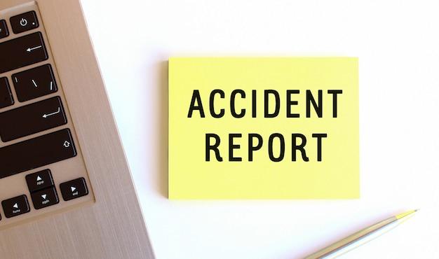 ノートパソコンの近くにある黄色の付箋紙に書かれた事故報告書