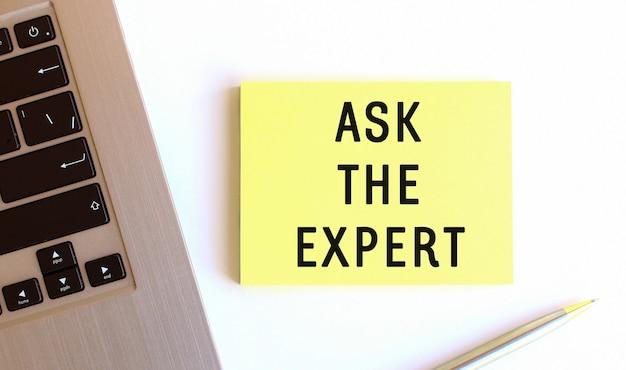 白いオフィスデスクのラップトップの近くにある黄色の付箋に刻まれた碑文は、専門家に尋ねます。