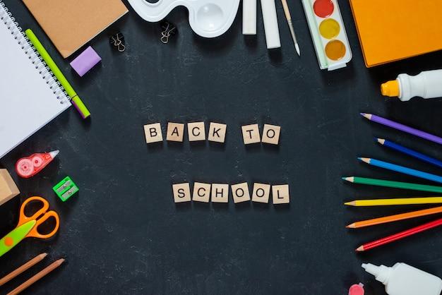 ブラックボードの背景に学用品の木製の手紙の碑文「学校に戻る」