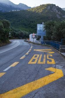 Надпись «автобус» ярко-желтой краской, нарисованная на асфальтированной дороге.