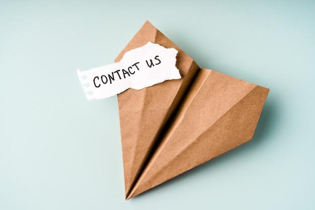 紙飛行機の横にある白い紙に「お問い合わせ」と書かれている
