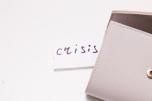 Надпись кризис на маленьком белом бумажке торчит из кармана кошелька.
