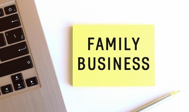 白いオフィスの机の上のラップトップの近くの黄色い付箋に刻まれたfamilybusiness。