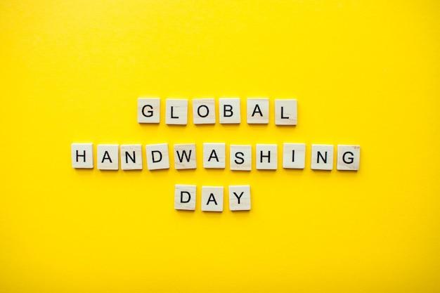 밝은 노란색 배경에 있는 나무 블록에서 글로벌 손 씻는 날