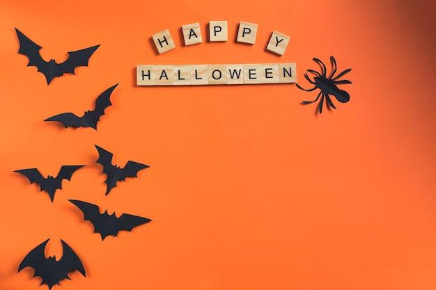 Надпись happy halloween из деревянных кубиков и летучих мышей, вырезанных из черной бумаги на оранжевом ба ...