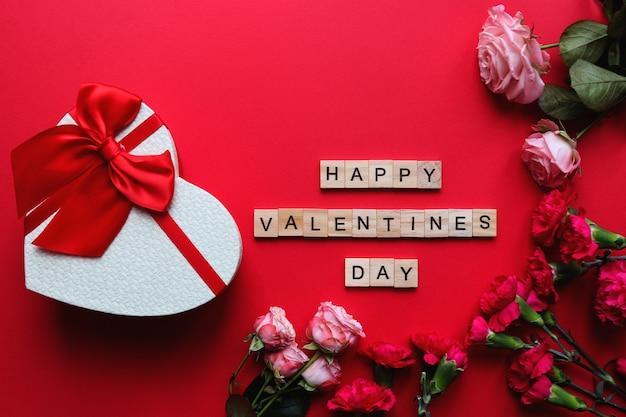 木製の文字、ハート型のギフトボックスと花から作られた碑文幸せなバレンタインデー
