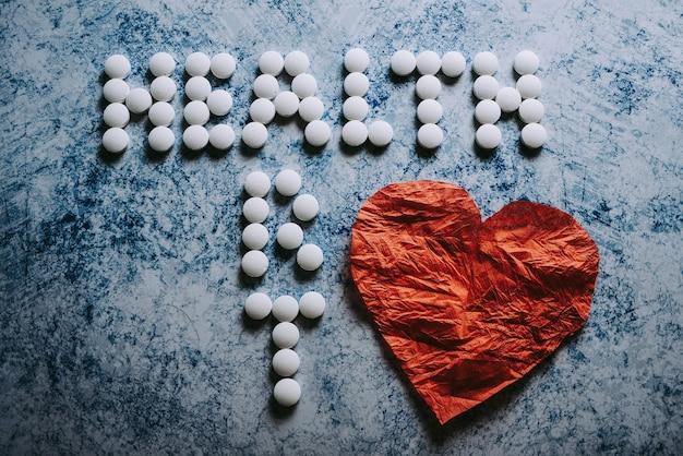 흰색 둥근 알약으로 늘어선 비문 건강과 냅킨에서 큰 붉은 심장