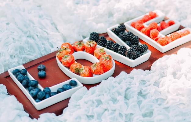 Надпись love из тарелок с сочными ягодами.