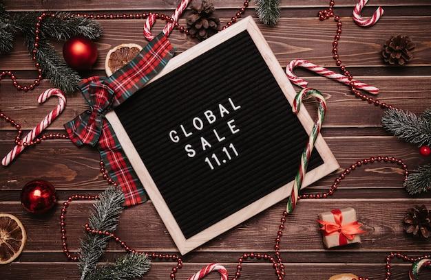 Надпись новогодняя распродажа 11.11 на доске объявлений. вокруг елочные игрушки, воздушные шары, еловые ветки, карамельные трости. вид сверху. готовая реклама глобальной распродажи 11 ноября.