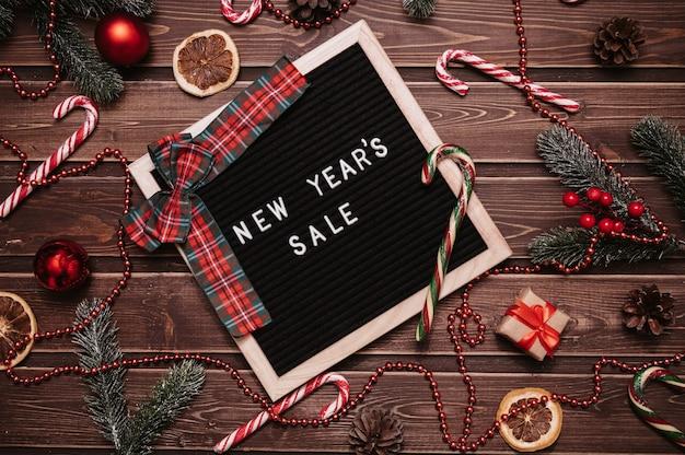 Надпись новогодняя распродажа на доске объявлений. вокруг елочные игрушки, воздушные шары, еловые ветки, карамельные трости. вид сверху. флэтли.
