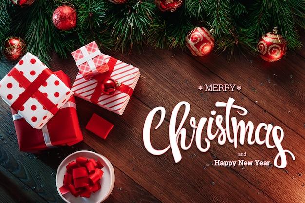 메리 크리스마스, 녹색 가문비 나무 가지, 헬기 및 나무 갈색 테이블에 선물의 비문. 크리스마스 카드, 휴일. 혼합 매체.